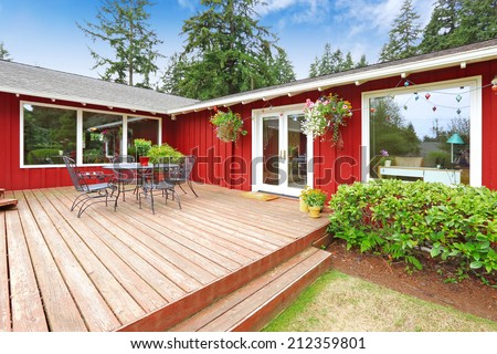 Beautiful bright red house with patio area and walkout deck - stock photo