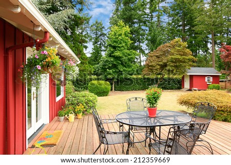 Beautiful bright red house with patio area on walkout deck and small red shed on backyard - stock photo