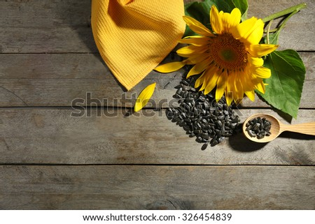 Beautiful bright sunflower with seeds on wooden table close up