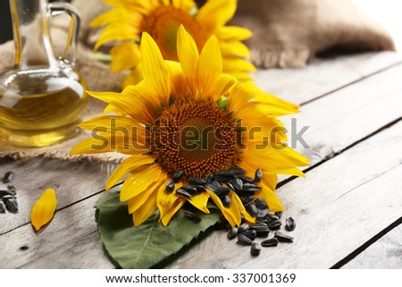 Beautiful bright sunflowers with seeds and bottle of oil on wooden table close up - stock photo