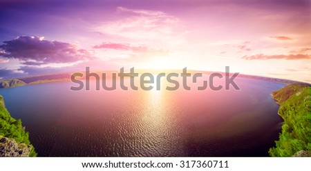 Beautiful bright sunset over the lake in mountains - stock photo
