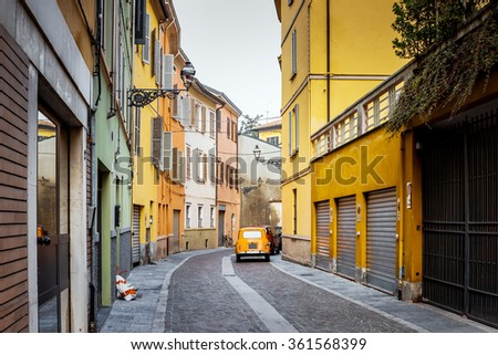 Beautiful bright turning street with vintage car in Parma, Italy.  Colorful buildings. - stock photo