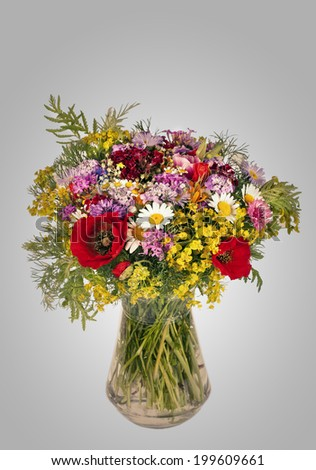 Beautiful Bright Wild flowers bouquet in vase. Cornflower, camomile, carnation, hand bell, poppy - stock photo