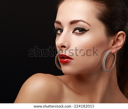 Beautiful bright woman makeup. Black eyeliner and red lips. Closeup on black background - stock photo