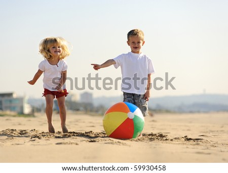 Beautiful brother and sister play with a beach ball outdoors - stock photo