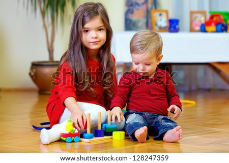 beautiful brother and sister playing at home - stock photo