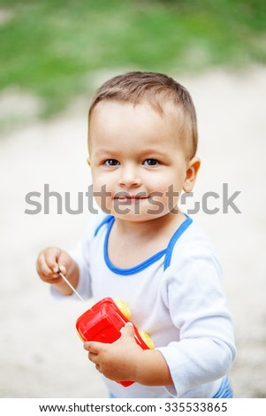 Beautiful brown-eyed little boy playing with a red plastic toy car outdoors - stock photo