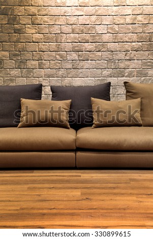 beautiful brown fabric sofa on wooden floor with brick wall. - stock photo