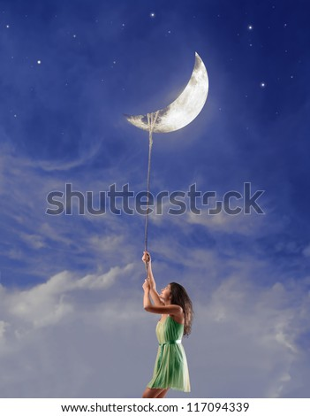Beautiful brown girl holding the moon with a rope - stock photo