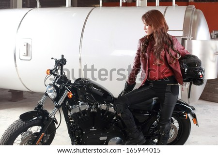 Beautiful brown hair female biker shot with studio flash. - stock photo