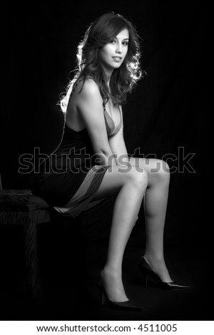 beautiful brown hair woman with sexy long legs wearing dress sitting on black background