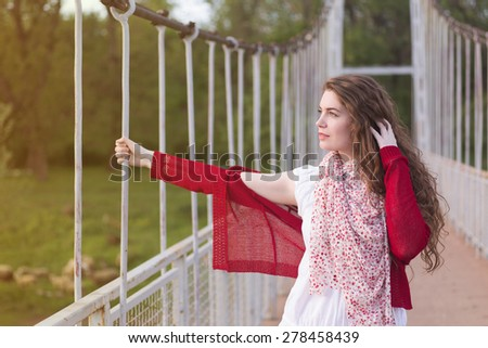 Beautiful brown-haired woman posing on the bridge. 'Hand in hair' pose. - stock photo