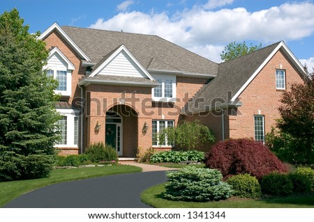Beautiful brown two story brick home with a circular driveway. Typical new home in the suburbs of the United States. Just one of many home or house photos in my gallery. - stock photo