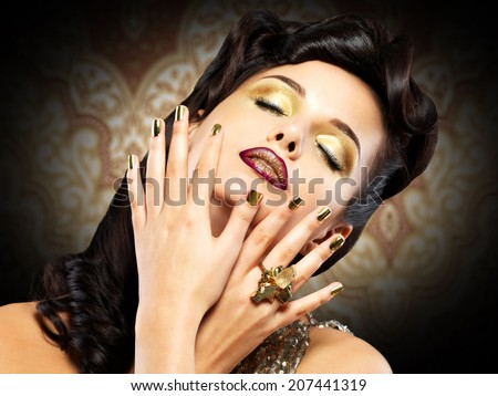 Beautiful brunet woman with golden nails over style background - stock photo