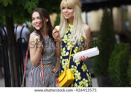 Beautiful brunette and blonde women walk in the street. Make shopping and talking. Day light. Life style.  - stock photo