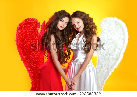 Beautiful Brunette Angel girls with angel's wings. Fashion women with long wavy hair wearing in red and white clothes. - stock photo