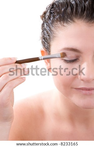 Beautiful brunette applying eye shadow to her eyelids with a soft brush - stock photo