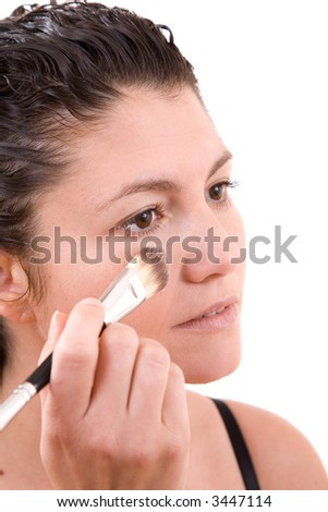 Beautiful brunette applying foundation with a big brush to her cheek on white background - stock photo