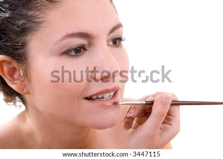 Beautiful brunette applying lipgloss to her lips with a small brush - stock photo
