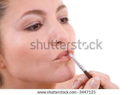Beautiful brunette applying lipstick with pouted lips on white background - stock photo