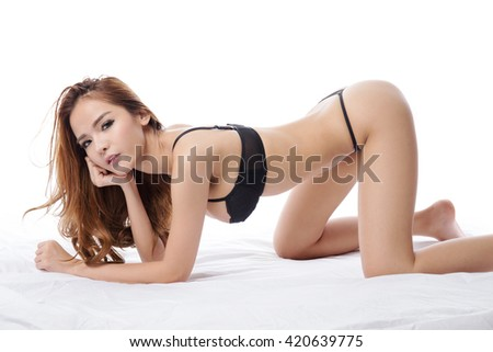 Beautiful brunette asian woman in lingerie and  thong, lying and posing in her bed, isolated on white background