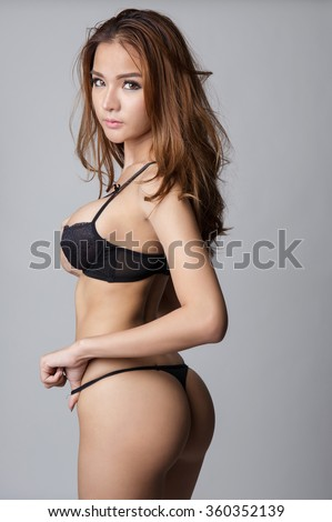 Beautiful brunette asian woman with nice body and buttocks in lingerie or thong. - stock photo