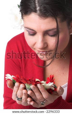 Beautiful brunette bend over the flowers in her hand to smell the scent - stock photo