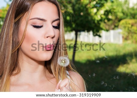 Beautiful brunette blowing dandelion - stock photo