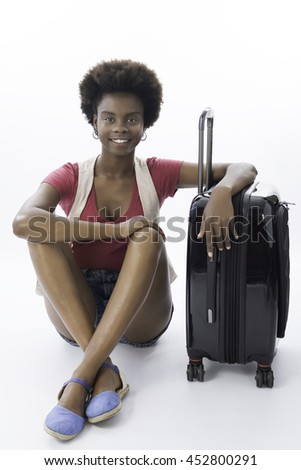 Beautiful brunette Brazilian woman, afro-descendant, seated on the floor, next to a suitcase, smiling and looking for the camera, in a white background. - stock photo