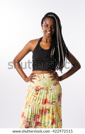 Beautiful brunette Brazilian woman, afro descendant, with long and braided hair, with her hands on hips, standing, looking for the camera and smiling, in a white background. - stock photo