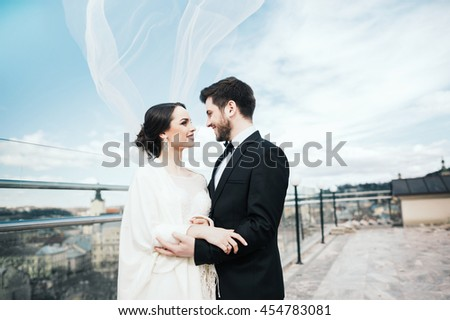 Beautiful brunette bride and bridegroom standing close to each other at old city background and smiling, wedding photo, copy space. - stock photo