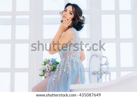 Beautiful brunette bride in wedding dress colors, serenity, sitting on the bathtub, dreaming about the groom. In a white Studio.