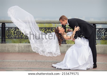 beautiful brunette bride in white wedding dress and flying veil hold her young handsome groom in black suit and stand on big city background