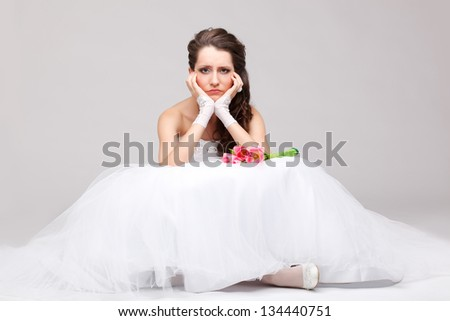 beautiful brunette  bride sitting on the floor and frowning