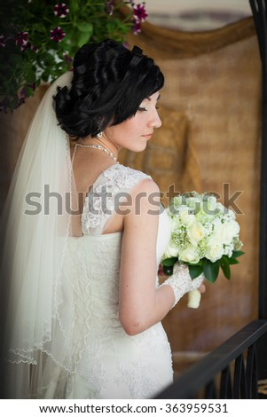 Beautiful brunette bride with white roses bouquet in vintage dre