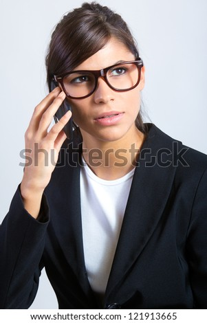 Beautiful brunette businesswoman talking by cellphone - stock photo