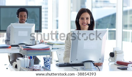 Beautiful brunette businesswoman working in a call center with a headset on - stock photo