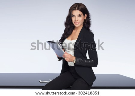 Beautiful brunette businesswoman working, looking at camera and smiling. Attractive woman holding tablet. Elegant style. Studio shot. - stock photo