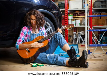 beautiful brunette car mechanic with a guitar sitting in a garage near the wheel of the car. lunch break in the workshop, a woman in blue overalls with a guitar