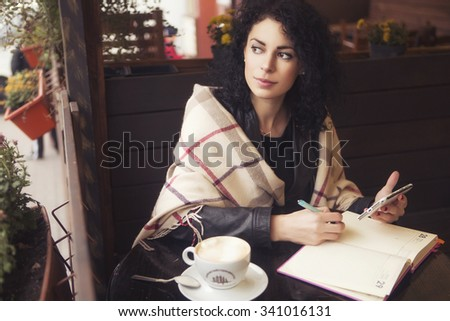 Beautiful brunette caucasian woman in leather jacket and plaid sitting on a cafe drinking coffee and working on her phone and notebook. cold weather - stock photo