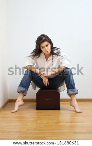 Beautiful brunette caucasian woman in white man`s shirt sitting on the coffer.