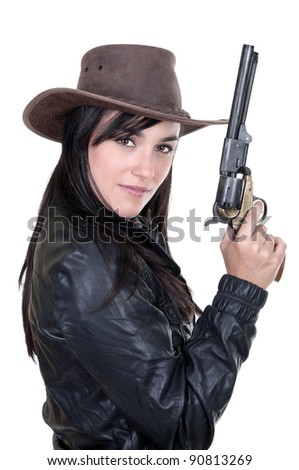 Beautiful brunette cowgirl model holding a gun, isolated on white - stock photo