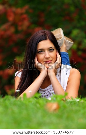 Beautiful brunette daydreaming in the park lying in the grass. - stock photo