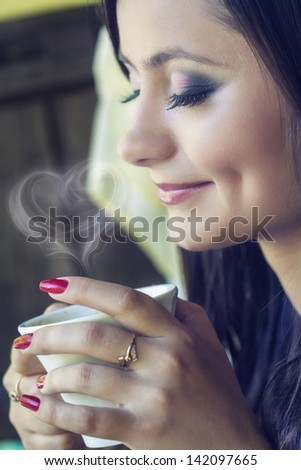 beautiful brunette drinking coffee in a restaurant outdoor - stock photo