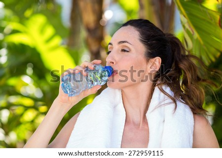 Beautiful brunette drinking water on a sunny day - stock photo