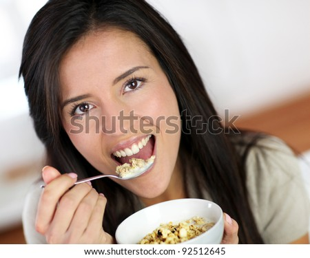 Beautiful brunette eating cereals in the morning