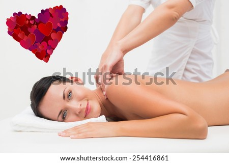 Beautiful brunette enjoying a back massage smiling at camera against heart - stock photo