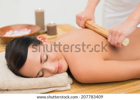 Beautiful brunette enjoying a bamboo roller massage in the health spa - stock photo