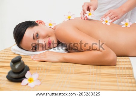 Beautiful brunette enjoying a flower back massage in the health spa - stock photo