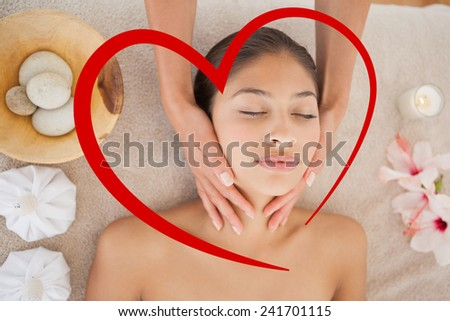 Beautiful brunette enjoying a head massage against heart - stock photo